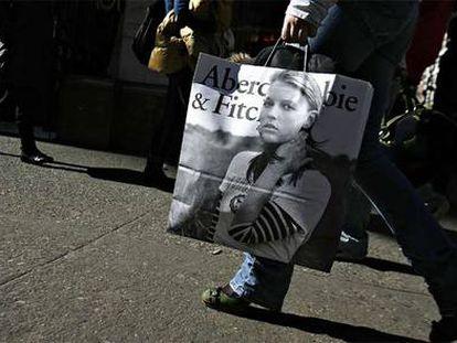 Una mujer camina con una bolsa de una tienda de Abercrombie.