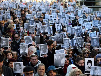 Los presentes en el acto muestran las fotos de las víctimas.