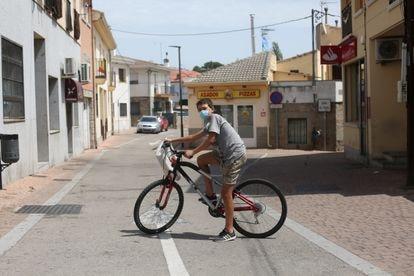 Un niño posa con su bici en las calles de Navalagamella.