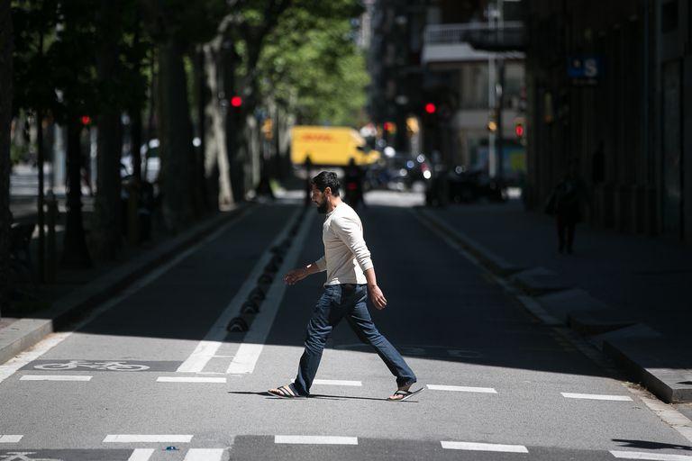 Un hombre cruza el carril lateral de la Gran Via de Barcelona, donde se cortará el tráfico para dar espacio a los peatones.