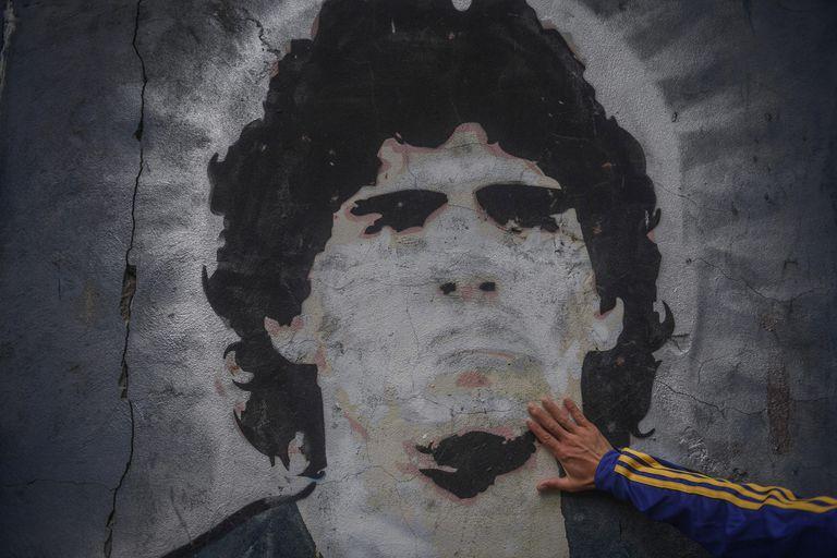 Un fan de Boca Juniors pone su mano en un mural de Diego Armando Maradona tras su muerte, el pasado miércoles.
