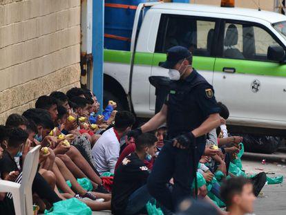 Menores migrantes comen manzanas el miércoles en Ceuta a la espera de que se les haga una prueba de covid-19.