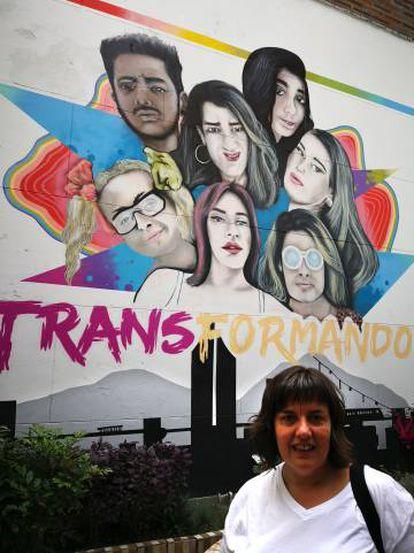 Natalia Aventín, madre de Patrick, junto a un cartel sobre transexualidad del centro LGTBI de Medellín (Colombia).