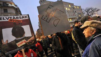 Manifestantes antigubernamentales portan una pancarta con las siglas de l partido oficial FIDESZ formando una esvástica, en una protesta el pasado 23 de diciembre.