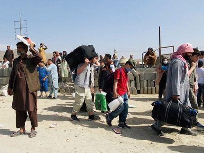 Un grupo de afganos que tratan de huir de Afganistán, ante el aeropuerto de Kabul este jueves.