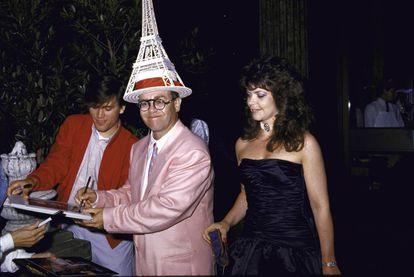 Elton John, con una Torre Eiffel en la cabeza, firma discos acompañado de su entonces esposa, Renate Blauer, en 1986.