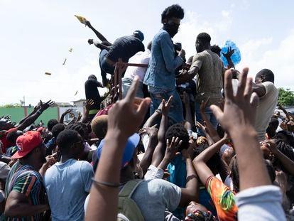 Personas que habitan el albergue en el estadio de futbol disputan por las bolsas de agua que han llevado las organizaciones de ayuda.