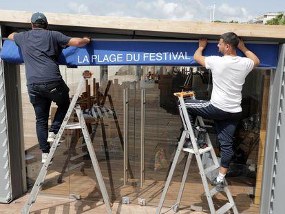 Trabajadores preparan las instalaciones de un club de playa en Cannes