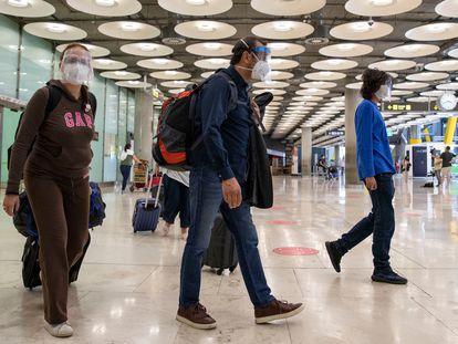 Varios pasajeros llegan al aeropuerto de Barajas, en Madrid, el pasado junio.