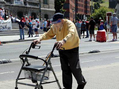 Un jubilado camina ante la concentración del movimiento de pensionistas de Bizkaia.
