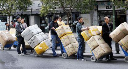 Comerciantes chinos transportan sus mercancías en el barrio madrileño de Lavapiés.