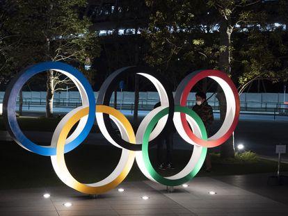 Dos hombres charlan tras los aros olímpicos junto al Nuevo Estadio Nacional en Tokio