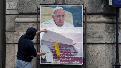 Un operario cubre un cartel contra el Papa en una calle de Roma.
