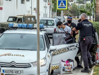 Agentes de la Policía Local de Ceuta introducen a dos inmigrantes en un coche, este miércoles.