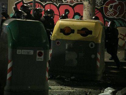 Agentes colocando contenedores después de que los lanzaran los okupas