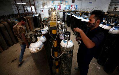 Operarios preparan botellas de oxígeno en Bangalore (India).