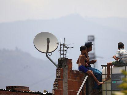 Unos niños juegan en un tejado junto a una antena de televisión por cable en el barrio caraqueño de Catia, este martes.