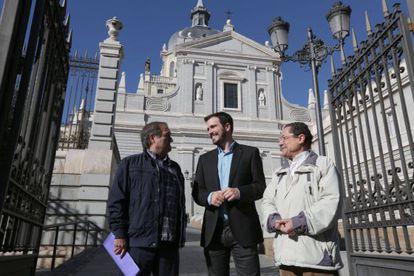 Alberto Garzón frente a la Catedral de la Almudena con dos representantes de Europa Laica.