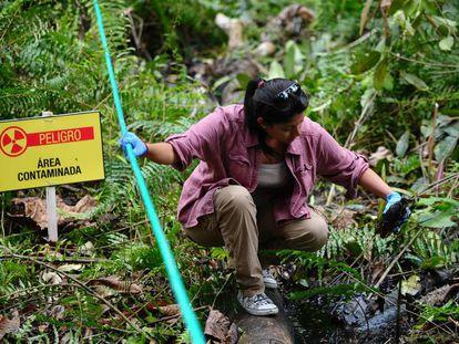 Una mujer muestra una botella cubierta con petróleo, en una imagen de 2013 en la región amazónica de Ecuador.