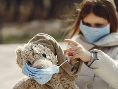 Una niña con mascarilla juega con su oso de peluche