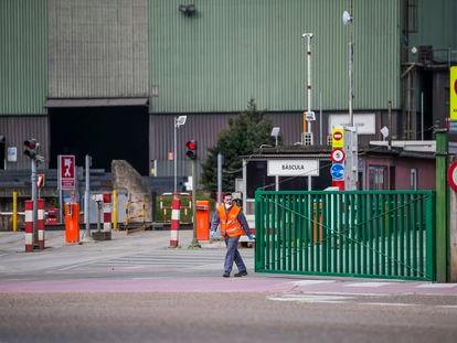 Un trabajador cierra la entrada de una fábrica, el 15 de marzo en Santander.
