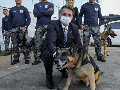 El presidente Bolsonaro, este lunes en Brasilia durante un acto con un perro policía y varios agentes.