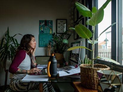 Una mujer realiza teletrabajo en su casa.