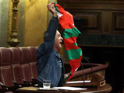 Sabino Cuadra exhibe una ikurriña desde la tribuna del Congreso.