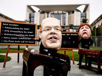 Activistas climáticos protestan con máscaras parecidas a la canciller alemana Angela Merkel (dcha) y el ministro de Economía alemán Peter Altmaier, frente a la Cancillería durante una reunión del Gabinete en Berlín, el 12 de mayo.