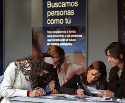 Alumnas universitarios rellenando formularios de empleo en la Universidad Politécnica.