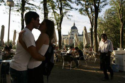 Dos jóvenes se besan en una terraza entre el paseo del Prado y la plaza de Oriente, detrás la catedral de La Almudena de Madrid.