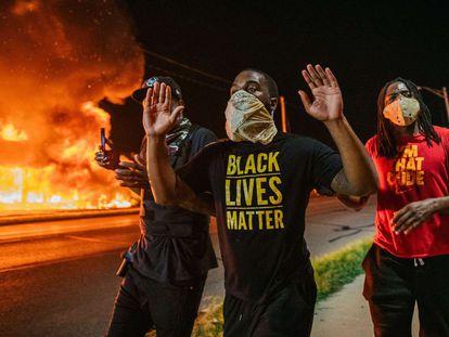 Tres hombres, durante las protestas en Kenosha (Wisconsin), la noche del lunes.