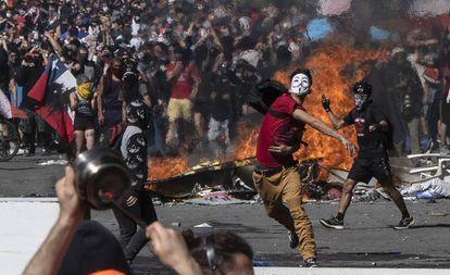 Un joven lanza piedras contra la policía durante una protesta en Santiago de Chile.
