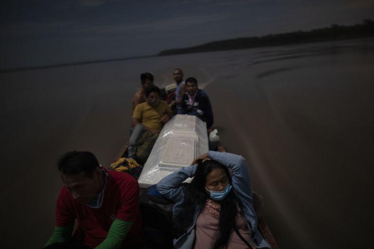 Algunos familiares llevan el feretro de un hombre que murió de complicaciones derivadas de la covid-19 por el río Ucayali de Perú.