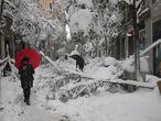 Varias personas pasean por la calle Fuencarral en Madrid, en la que numerosos árboles y parte de la iluminación de navidad no han resistido el peso de la nieve.