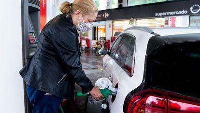 Una mujer reposta su vehículo en una gasolinera de Madrid.