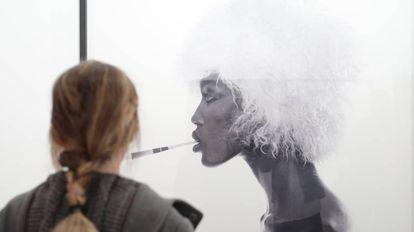 Una mujer mira el retrato de Naomi Campbell, de Comte.