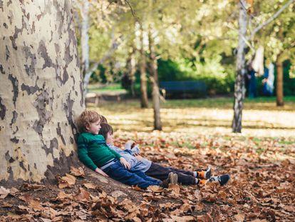 Tres niños reflexionan apoyados en un árbol.