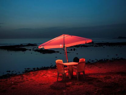 Una mesa y unas sillas de plástico junto al mar, en Trípoli, Líbano.