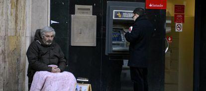 Un hombre pide a la puerta de una sucursal bancaria en Madrid.