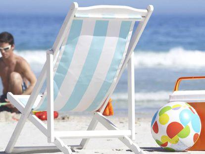 Una nevera de playa y un balón inflable descansan al lado de una silla en la orilla.