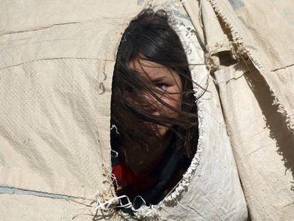 Una niña afgana desplazada que huyó de su casa debido a los enfrentamientos entre los talibanes y el personal de seguridad afgano, permanece en su tienda de campaña improvisada en un campamento en las afueras de Mazar-e-Sharif, en el norte de Afganistán.