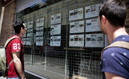 Dos personas observan el escaparate de una empresa inmobiliaria.