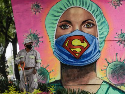 Un jardinero con mascarilla trabaja junto a un mural, en Ciudad de México.