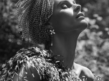 Vestido en crepé de seda negra rematado en plumas blancas y negras de Antonio García, pendiente largo con pétalos de cristal blanco y azul de Swarovski, y tocado de plumas blancas y negras de Heritage.