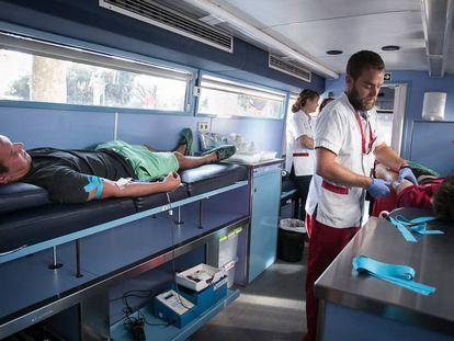Dos hombres donando sangre este verano.