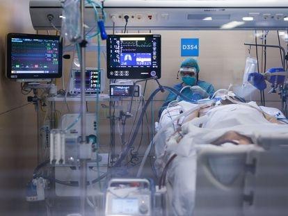 Un trabajador sanitario atiende a un enfermo de Covid-19 en la Unidad de Cuidados Intensivos del hospital Vall d'Hebron, en Barcelona.
