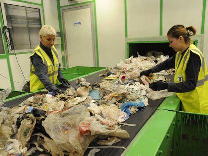 Dos trabajadoras separan basura antes de reciclar el plástico.