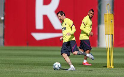Messi, con la pelota, en un entrenamiento del Barcelona, ante la mirada de Arturo Vidal.