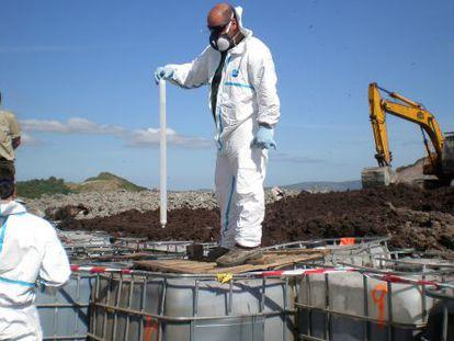 Unos técnicos de Medio Ambiente de la Junta de Andalucía analizan bidones de residuos en el vertedero de Gamasur (Cádiz).